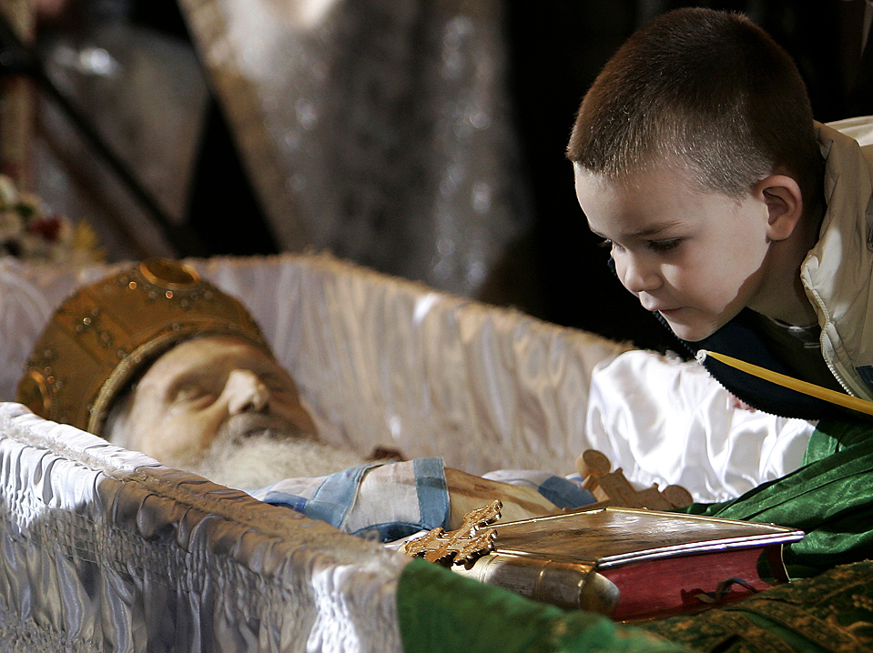 A boy reacts near the coffin of Patriarch Pavle as he lies in repose at the Congregational church, in Belgrade, Serbia, Tuesday, Nov. 17, 2009. Patriarch Pavle, who led Serbia's Christian Orthodox Church through its post-Communist revival and called for peace and conciliation during the Balkan conflicts of the 1990s, died Sunday. (AP Photo/Darko Vojinovic)